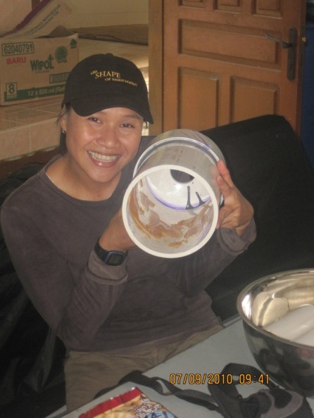 """Ibu Maryanti holding a """"termite feeder tube"""" that is strong enough to stand up to the large males. This one is filled with peanut butter and ready to be closed so that the males must access the peanut butter with a stick through the smaller hole."""