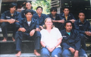 Photographic Memories: Pak Ateng (top row, far right with a yellow shirt showing under his uniform) back when he first started working at the OFI Care Center. (Western visitor is in center).
