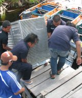 OFI staff bring up orangutan transport cage from river into release camp at Lamandau Reserve
